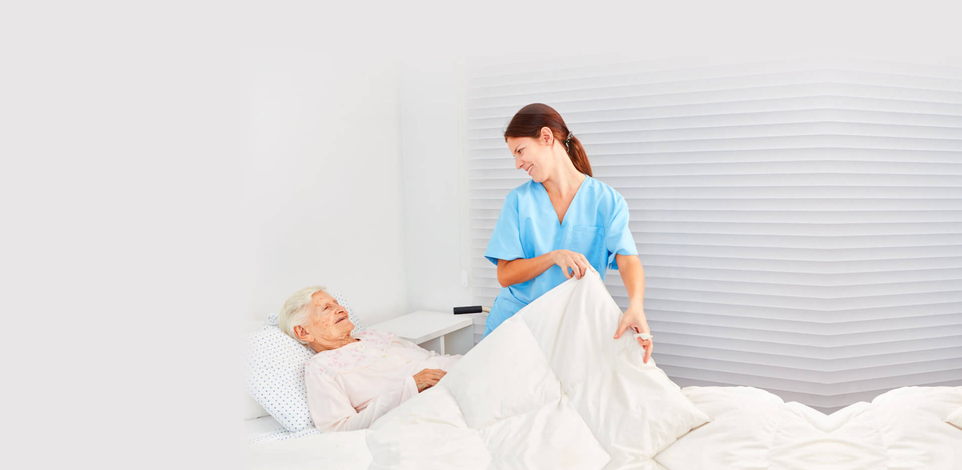 senior woman going to sleep while caregiver giving her blanket