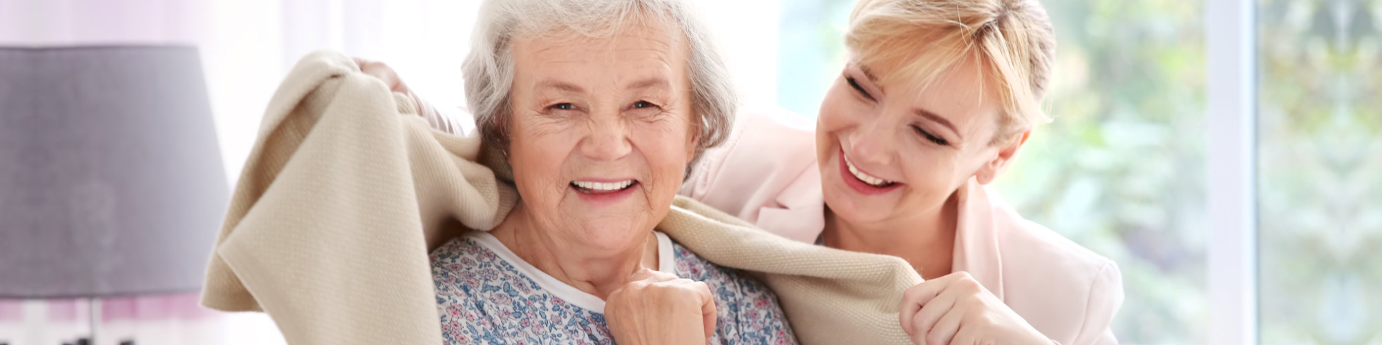 photo of a caregiver giving blanket to a senior woman
