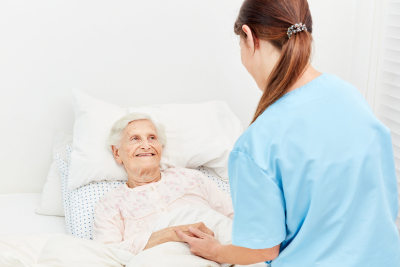 Old women in hospice or nursing home is being comforted by a nurse
